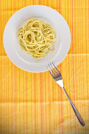 A plate of spaghetti pasta on a yellow tablecloth with pesto and a silver fork - above view photo