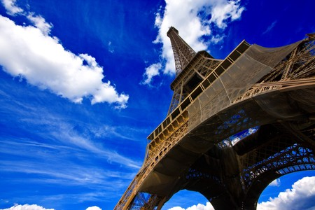 Eiffel tower in Paris, France, against an intense blue sky with white clouds photo