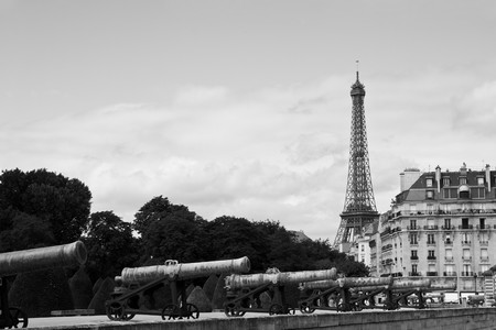 Vintage Paris shot - Eiffel Tower from les invalides with series of cannons on foreground. Black and White photo