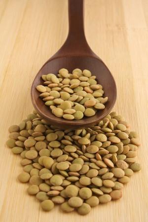 lenteja: Lentejas verdes en una cuchara de madera