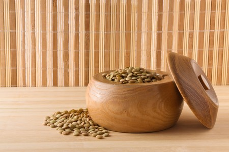 Green lentils in a wooden bowl - bamboo mat as background, with copy space photo