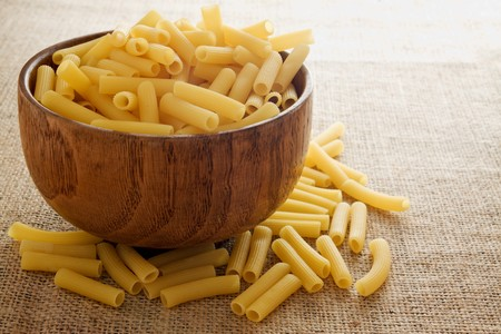 Uncooked pasta in a wooden bowl on burlap background photo