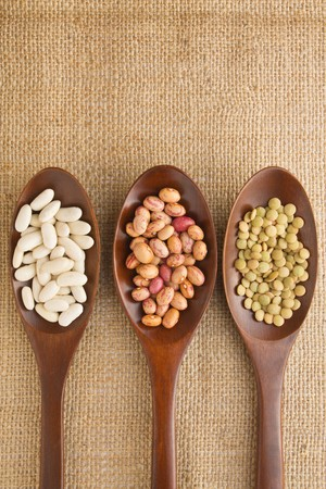 Three wooden spoon on burlap with beans and lentil. photo
