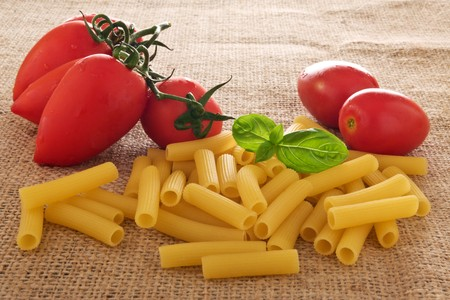 Raw pasta with fresh red tomatoes and basil on burlap photo