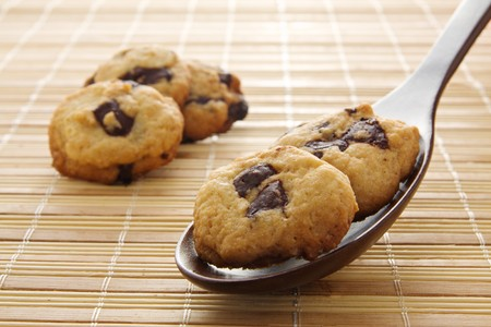Several chocolate chip cookie, two on a wooden spoon, on a bamboo mat photo