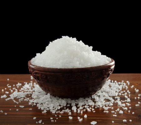 black sea: Sea salt in a bowl, isolated on black background Stock Photo
