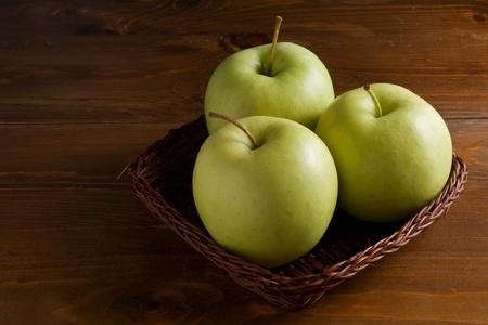 Three fresh green apples in a wicker basket photo