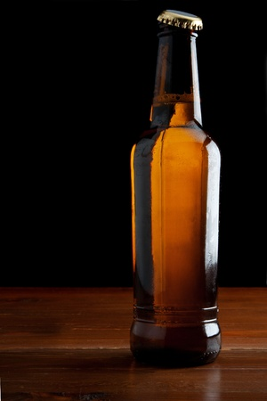 A Beer bottle on a wooden table - isolated on black photo