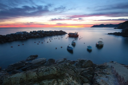 Beautiful view of the sea at twilight in Riomaggiore, Italy - blurred boat due to long exposure photo