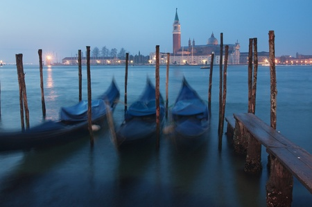 venezia: View of Venice, Italy at dusk - three gondolas in front of the San Giorgio Maggiore island Stock Photo