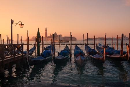 Gondolas in venice at sunset - San Giorgio maggiore on background photo