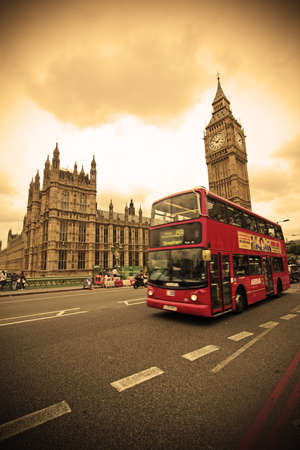 vintage: Londen, Verenigd Koninkrijk - 12 juli 2011: rode dubbeldekker bus passeert op Westminster Bridge. Houses of Parliament en de Big Ben op de achtergrond. Rode bussen zijn iconische symbolen van Londen. Redactioneel