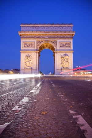 Arc de Triomphe: Front view of Arc de Triomphe (Arch of Triumph) in Paris at dusk - vertical shot Stock Photo