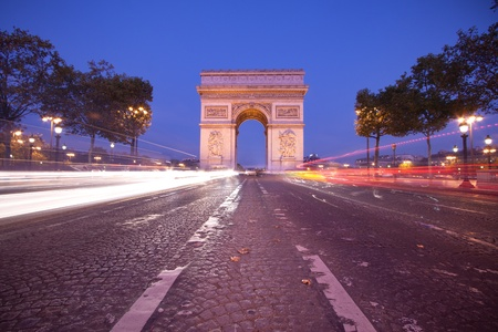 parisian: Front view of Arc de Triomphe (Arch of Triumph) in Paris at dusk with traffic light trail Stock Photo