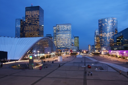 Illuminated office buildings in La Defense, French financial district in Paris, at dusk
