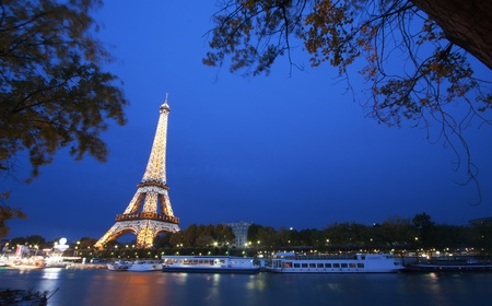 PARIS - October 25: Eiffel Tower light show at dusk with Seine river on foreground on October 25, 2011 in Paris, France. Eiffel Tower is the highest and most visited monument in France and use 20,000 light bulbs in the night show.