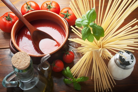 eating pasta: Tomato sauce on a terracotta pot with ingredients and spaghetti pasta seen from above.