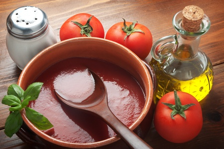 Tomato sauce on a terracotta pot with ingredients seen from above. photo