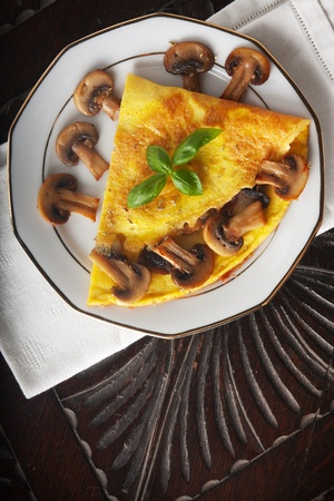 omelet: Omelet with mushroom on a wooden table seen from above
