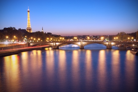Paris, France - October 23 2011: Seine River and Eiffel Tower at dusk. The Eiffel tower is the most visited monument of France.