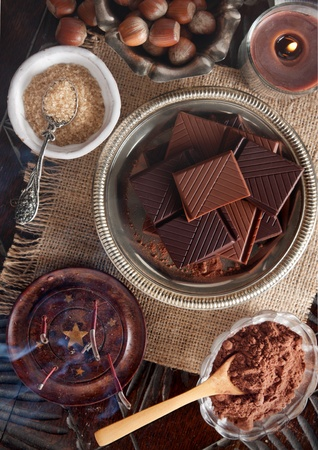 bar top: Chocolate bars and ingredients on a wooden table seen directly from above Stock Photo