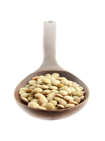 green lentil: Green lentil on a wooden spoon isolated on white background - Shallow depth of field Stock Photo