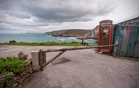 british english: Iconic British Red Phone Box in a remote landscape. Photo taken in Cornwall, England. Stock Photo