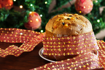 A traditional panettone, the famous italian Christmas cake. Blurred Christmas tree on background and decoration. Stock fotó