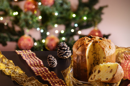 A traditional panettone, the famous italian Christmas cake on a wooden table. Blurred Christmas tree and decoration on background .