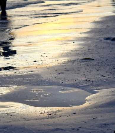 A puddle formed at the beach at sunset Imagens