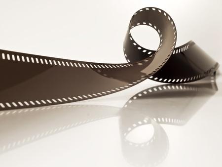 videofilm: etwas gerollt unbebauten Film-Streifen auf eine gl�nzende Oberfl�che Lizenzfreie Bilder