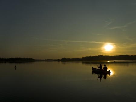 bateau de peche: deux personnes assis dans un bateau et face � l'aube Banque d'images
