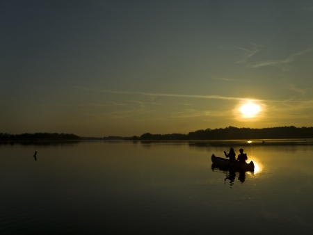 two persons sitting in a boat and facing dawn photo
