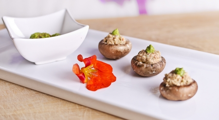 raw food mushrooms with nut filling and green pesto on top photo