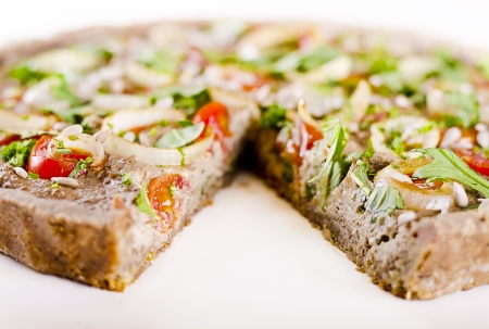 vegan raw food quiche with nut filling and vegetables on top photo