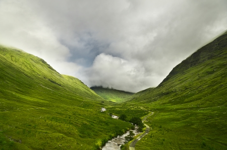 River flowing through a valley in the scottish highlands, the mountains are covered in clouds photo