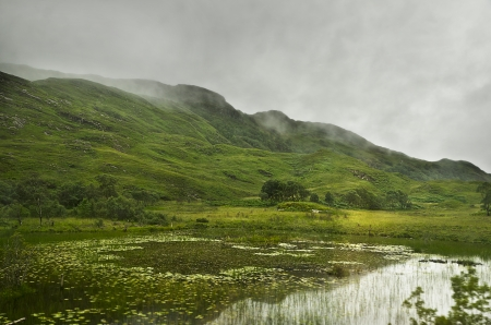 foggy mountains in the scottish highlands with a lake in front photo
