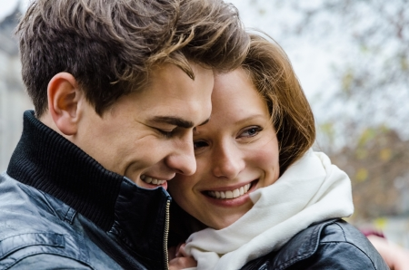 man woman hugging: Closeup of happy young couple embracing each other outdoors