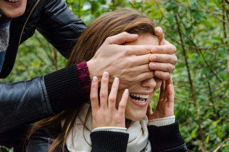 Cropped image of mans hands covering womans eyes in park photo