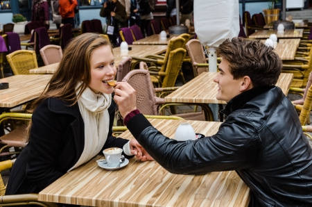 outdoor restaurant: Loving young man feeding biscuit to woman at outdoor restaurant table Stock Photo