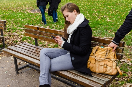 Pickpocket stealing handbag while woman using mobile phone on bench in park photo
