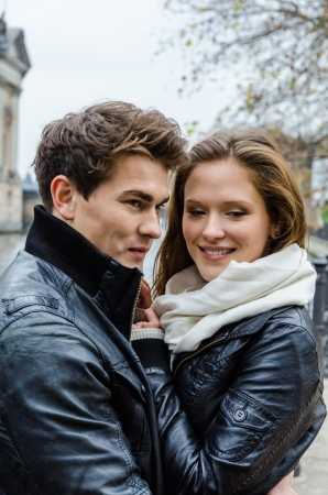 waistup: Young couple in winter jackets embracing each other outdoors