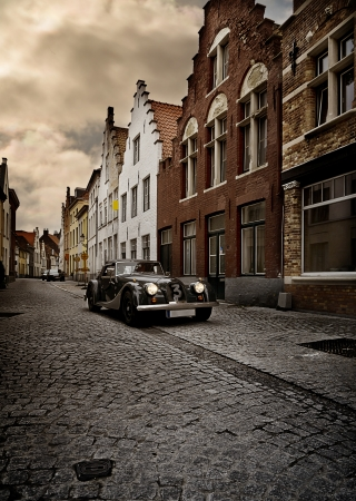 old vintage car driving through the medieval city of Bruges, Belgium