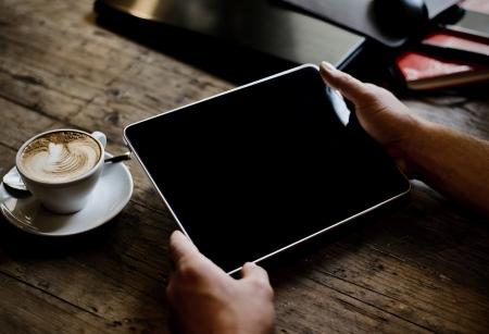 Hände eines Mannes hält leere Tablet-Gerät über eine hölzerne Arbeitsbereich-Tabelle Standard-Bild