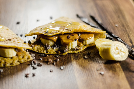 choco chips: Closeup of banana pancakes wit choco chips on wooden table