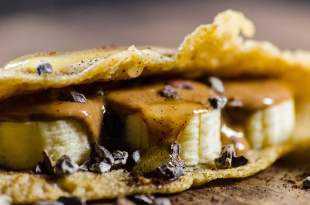 choco chips: Closeup of pancake made with bananas; choco chips and syrup on table