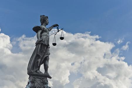 estatua de la justicia: Estatua de la Justicia con la espada y las escalas en frente de un cielo nublado azul Foto de archivo
