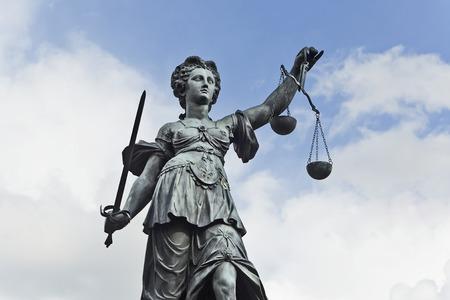 Standbeeld van Justitie met zwaard en schalen in de voorkant van een blauwe bewolkte hemel Stockfoto