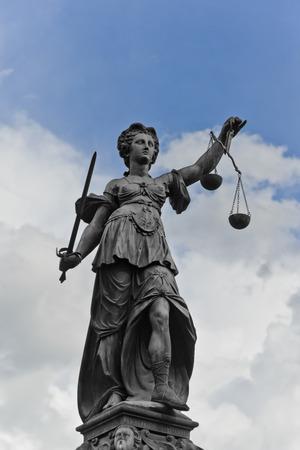 dama de la justicia: Estatua de la Justicia con la espada y las escalas en frente de un cielo nublado azul Foto de archivo