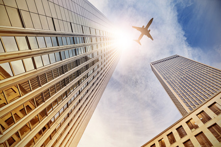 plane flying over office buildings in Frankfurt am Main, Germany photo